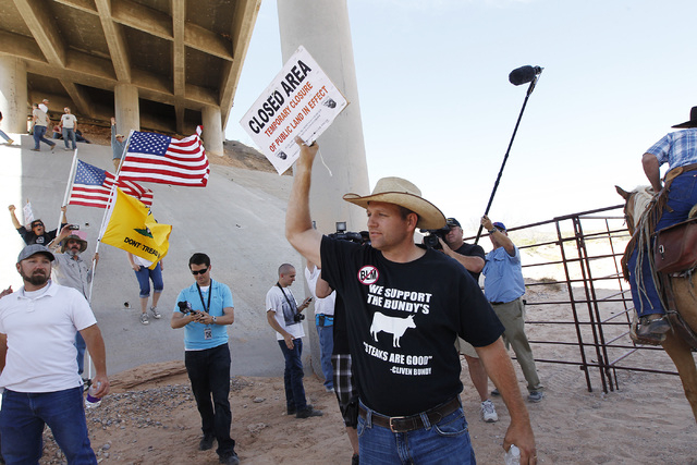 "Ammon Bundy, middle, son of rancher Cliven Bundy, removes a ""closed area"" sign from the BLM impound corral after the BLM agreed to release his family's a cattle near Bunkerville on April ..."