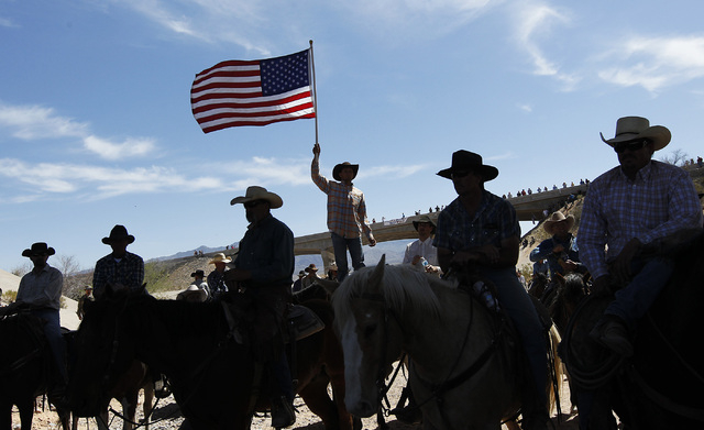 A supporter of the Bundy family flies the American flag after the BLM agreed to release the Bundy's cattle near Bunkerville April 12, 2014. (Jason Bean/Las Vegas Review-Journal)