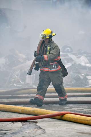 A firefighter carries a hose at a fire at SA Recycling in North Las Vegas on Friday, April 11, 2014.  Several dozen firefighters from North Las Vegas, Clark county, Las Vegas and Nellis Air Force  ...