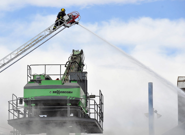 A firefighter atop a latter works to contain a fire at SA Recycling in North Las Vegas on Friday, April 11, 2014.  Several dozen firefighters from North Las Vegas, Clark county, Las Vegas and Nell ...