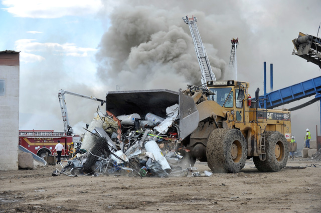 A worker uses a front end loader to move scrap material that caught fire at SA Recycling in North Las Vegas on Friday, April 11, 2014.  Several dozen firefighters from North Las Vegas, Clark count ...