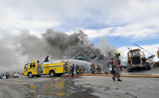 Firefighters work to contain a fire at SA Recycling in North Las Vegas on Friday, April 11, 2014.  Several dozen firefighters from North Las Vegas, Clark county, Las Vegas and Nellis Air Force bas ...