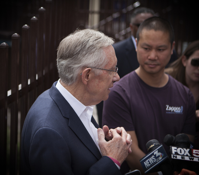 U.S. Sen. Harry Reid, D-Nev., left, discusses the Cliven Bundy standoff with the Bureau of Land Management while touring downtown Las Vegas with Tony Hsieh, CEO of Zappos, on Tuesday, April 15, 20 ...