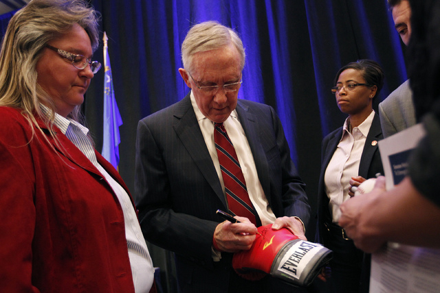 U.S. Sen. Harry Reid, D-Nev., signs a boxing glove after the Las Vegas Review-Journal's Hashtags & Headlines event at Paris Hotel & Casino in Las Vegas on Thursday. (John Locher/Las Vegas Review-J ...