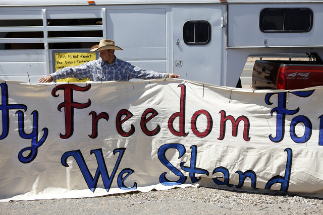 "John Banks holds up a banner during a rally in support of Cliven Bundy near Bunkerville Nev. Monday, April 7, 2014, 2014. The Bureau of Land Management has begun to round up what they call ""t ..."