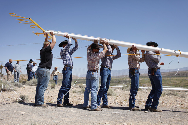 People help erect a pole to hang a banner during a rally in support of Cliven Bundy near Bunkerville Nev. Monday, April 7, 2014, 2014. The Bureau of Land Management has begun to round up what they ...