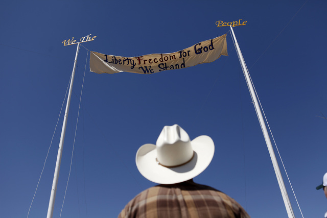 "A man looks at a banner during a rally in support of Cliven Bundy near Bunkerville Nev. Monday, April 7, 2014, 2014. The Bureau of Land Management has begun to round up what they call ""trespa ..."