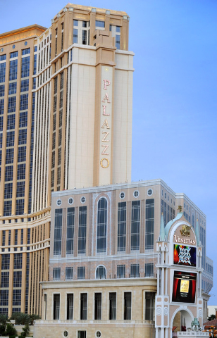 The unfinished tower is seen in the shadows of The Palazzo, known as the St. Regis Residences condominiums, is covered with giant sheets of cloth printed with the image of a completed building on  ...