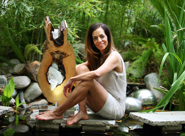 """Dorit Schwartz sits with her sculpture titled """"Spiritual Awakening,"""" made of acacia and quartz, at a pond in her backyard, March 10. (Ronda Churchill/View)"""