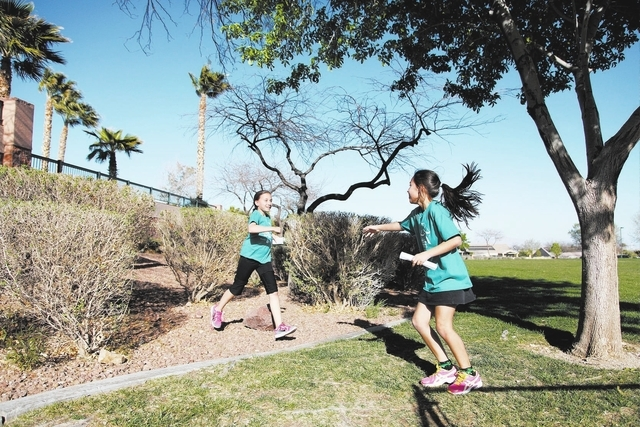 Daytona DeLeon, right, encourages teammate Kate Carvalho during their run at Tree Top Park, 600 Sageberry Drive, as part of the Girls on the Run program. (Alex Federowicz/View)