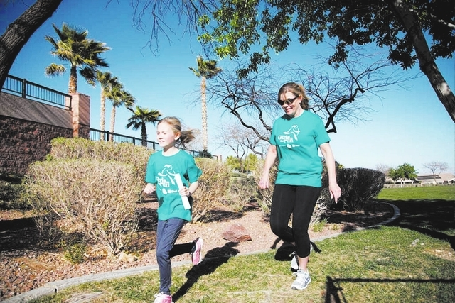 Coach Teri Heinz encourages Hannah Mallon as they run at Tree Top Park, 600 Sageberry Drive, as part of the Girls on the Run program. (Alex Federowicz/View)