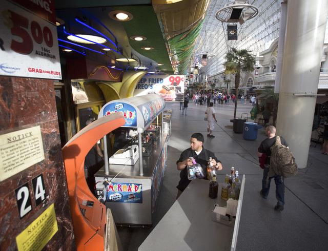 Jacob Tuitele stocks a portable bar in front of Mermaids Casino on Fremont Street Experience on Thursday, April 3, 2014. An ordinance was introduced Wednesday allowing two permanent outdoor bars t ...