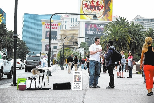 Ed Graveline, left, regional director of the St. Paul Street Evangelization offers rosaries to tourists along the Las Vegas Strip on Saturday, Feb. 15, 2014. Graveline and his team of street evang ...