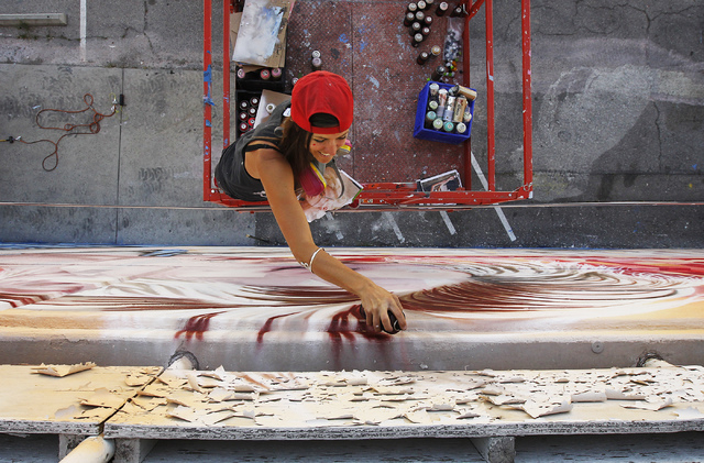 With some of the building's old paint pealing off in the foreground, street artist Christina Angelina, from Venice, Calif., paints a mural on the west side of the now closed Western Hotel and Casi ...