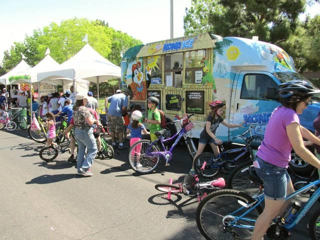 Cyclists take a break at the Kona Ice truck during Henderson Stroll 'n Roll  April 12.