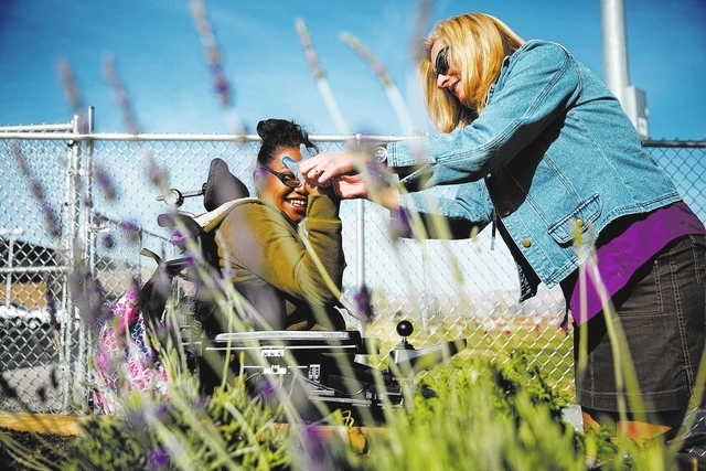 Desert Oasis High School special education teacher Jennifer Davis, right, helps Carianne Bin put on a gardening glove. (Samantha Clemens/View)