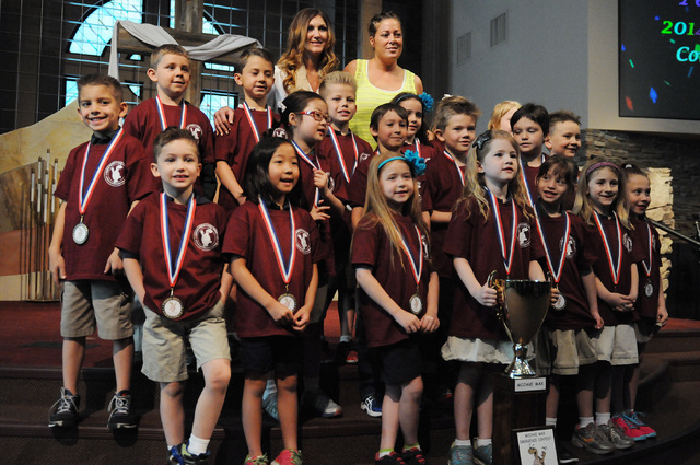 First grade student Peyton Burns, bottom row holding the trophy, poses for a class photo after Burns was announced the winner of the Mojave Max contest during a surprise ceremony at Faith Lutheran ...