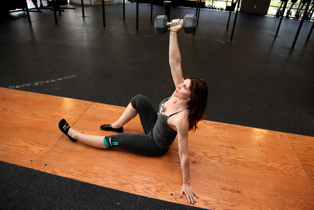 Trainer Laura Salcedo demonstrates the finishing position for the dumbbell crunch at CrossFit Mountain's Edge in Las Vegas on Tuesday, April 22, 2014. (Justin Yurkanin/Las Vegas Review-Journal)