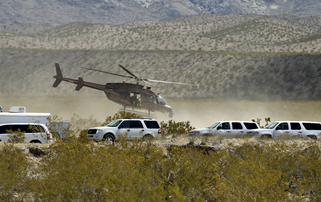A helicopter takes off from a staging area of Bureau of Land Management vehicles and other government vehicles off of Riverside Road near Bunkerville on Saturday. The Bureau of Land Management has ...