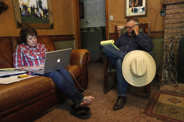 "Cliven Bundy, right, and his wife, Carol, make calls and look online at their ranch near Bunkerville on Saturday. The Bureau of Land Management has begun to round up what they call ""trespass cattl ..."