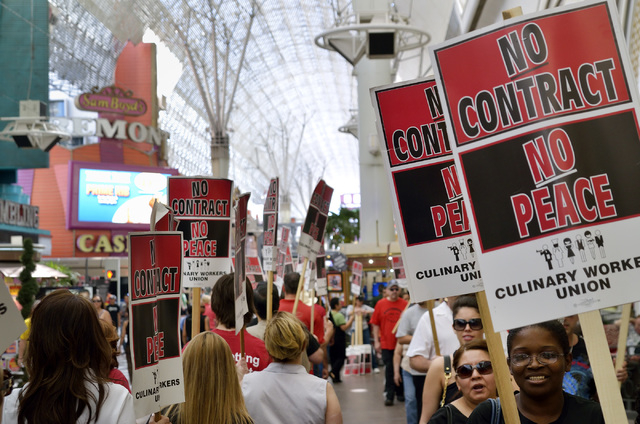 "Culinary and Bartenders Union supporters picket at the Fremont Street Experience in downtown Las Vegas on April 12, 2014. The unions, which aren't officially on strike, staged the ""informational p ..."