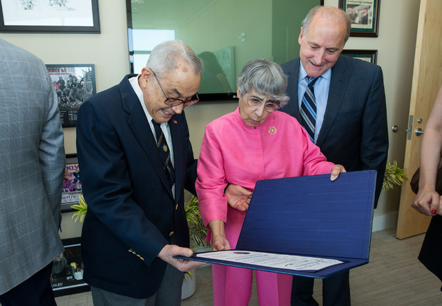 Jerry Vallen, co-founder of UNLVino, left, his wife Flossie Vallen, and Dean of William F. Harrah College of Hotel Administration, Stowe Shoemaker, look over a proclamation for UNLVino Week Thursd ...