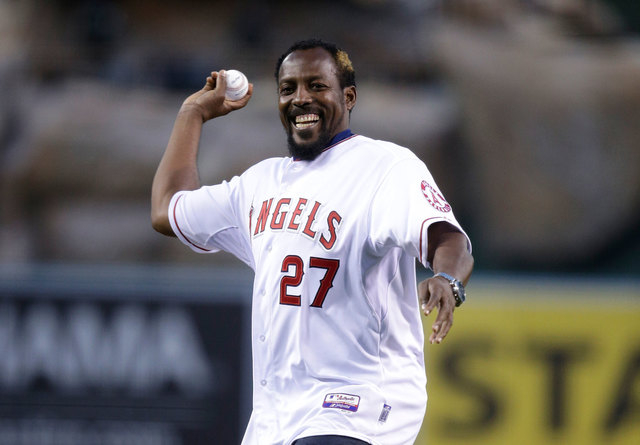 Vladimir Guerrero throws the ceremonial first pitch before an opening day baseball game between the Los Angeles Angels and the Seattle Mariners on Monday in Anaheim, Calif. Guerrero signed a one-d ...