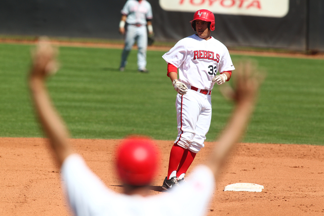 UNLV head coach Tim Chambers signals to outfielder Jonathan Torres (33) as he makes it to second base while playing New Mexico in the sixth inning during a baseball game at Earl E. Wilson Stadium  ...