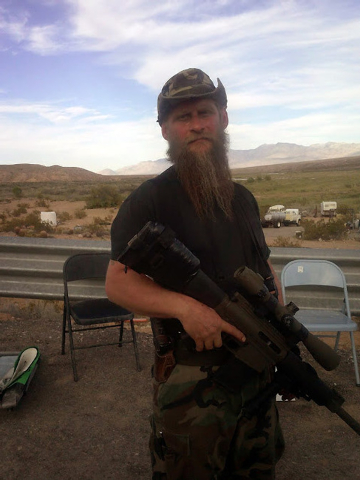 Jim Lardy, 49, of Philipsburg, Mont., a member of the West Mountain Rangers, poses holding his LR-308 rifle. He is one of a handful of militia who have come to the Bundy ranch from across the U.S. ...