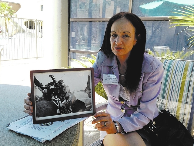 Tara O'Grady holds a photograph Saturday of her father, Vietnam War pilot John O'Grady, during a break in a meeting with Pentagon officials in Las Vegas about recovering remains of missing militar ...