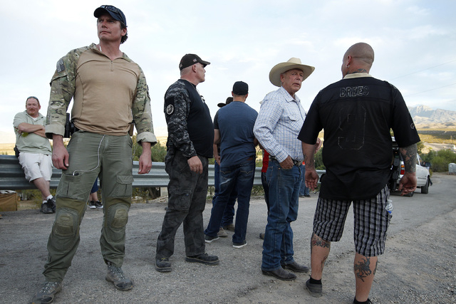 Cliven Bundy, second from right, stands with bodyguards near Bunkerville, Nev. Friday, April 11, 2014. The area has become the center of a protest against the Bureau of Land Management's roundup o ...