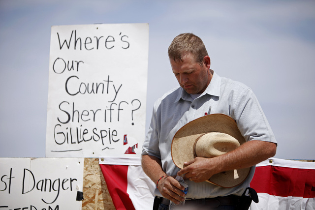 Ammon Bundy lowers his head for a prayer near Bunkerville, Nev. Friday, April 11, 2014. The area has become the center of a protest against the Bureau of Land Management's roundup of what they cal ...