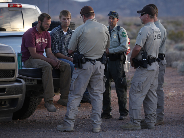 Tyler Shillig, left, and Spencer Shilling sit on a truck before they are released by federal law enforcement officers at the Lake Mead National Recreation Area near Overton on Thursday, April 10,  ...