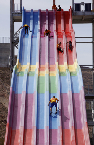 Employees apply wax to prepare the Desert Racers water slide for use at Wet'n'Wild in Las Vegas Tuesday, April 8, 2014. The water park will open for visitors on Saturday. (John Locher/Las Vegas Re ...
