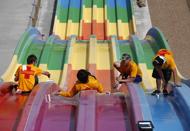 Employees apply wax to prepare the Desert Racers water slide for use at Wet'n'Wild in Las Vegas Tuesday, April 8, 2014. The water park will open for visitors on Saturday. (John Locher/Las Vega ...