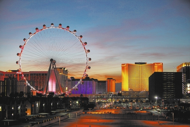 The 550-foot-tall High Roller lights up at dusk along the Strip on Friday. The 28-pod observation wheel is expected to open in April. (John Locher/Las Vegas Review-Journal)
