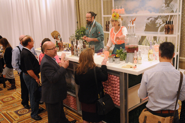 Adam Rains, rear left, and Emily Ellyn, rear right, mix drinks at the LiDestri Spirits booth during the Wine & Spirits Wholesalers of America's 71st annual convention at the Caesars Palace in Las  ...