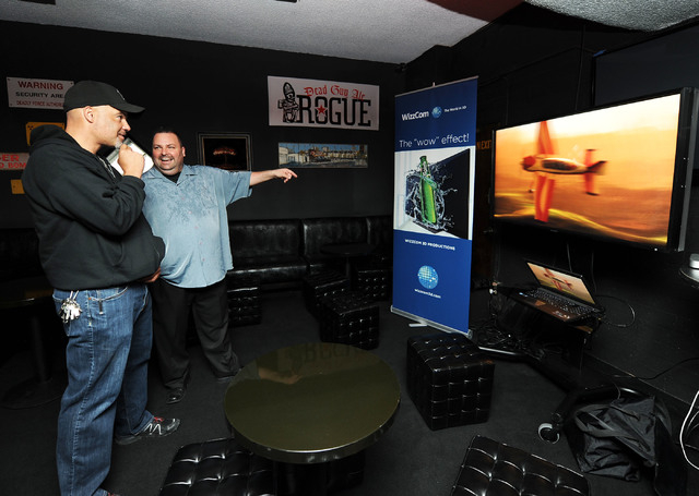 Freeman White, III, left, and Paul Clark, U.S. sales manager for WizzCom 3D Productions, watch the 3-D effects on a monitor as the system is previewed in Atomic Liquors on Wednesday. The company's ...