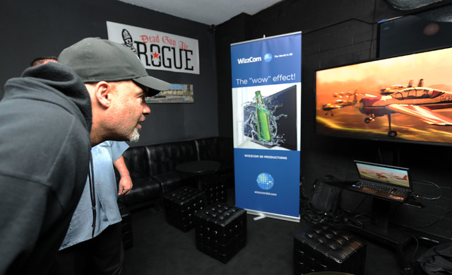 Las Vegan Freeman White III watches the 3-D effects on a WizzCom 3D Productions monitor as the system is previewed in Atomic Liquors on Wednesday. (Jerry Henkel/Las Vegas Review-Journal)