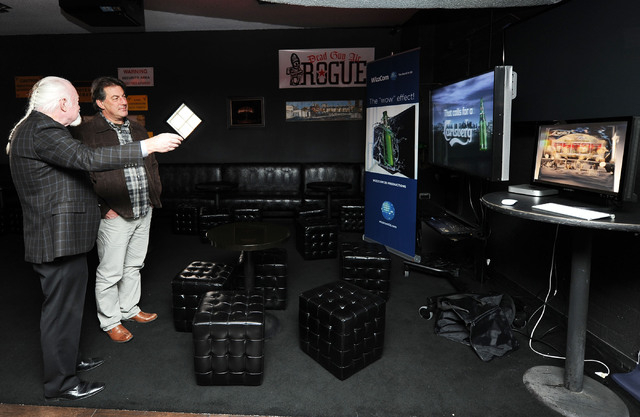 Michael Flynn, senior consutant for WizzCom 3D Productions, left, explains the 3-D effects to Pete Korner of Las Vegas as they watch on a monitor as the system is previewed in Atomic Liquors on We ...