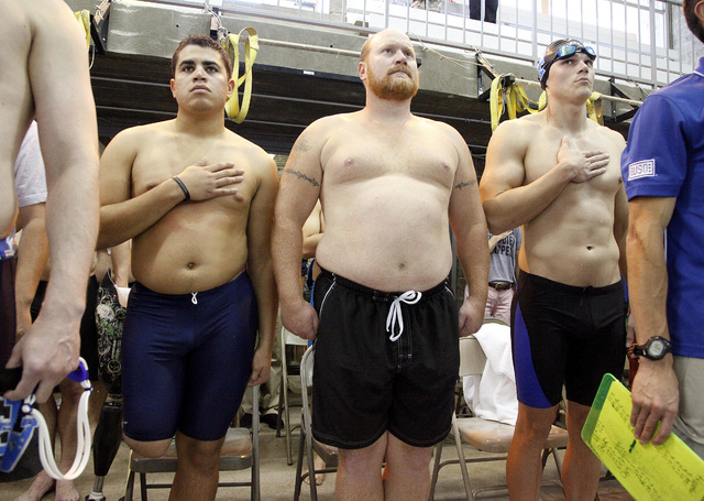 Air Force Staff Sergeant Mark Johnson, left, and Tony Anderson, center, stand during the national anthem before the start of the inaugural Air Force Trials at the Buchanan Natatorium on the campus ...