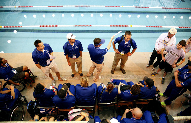 Event officials talk with competitors at the beginning of the inaugural Air Force Trials at the Buchanan Natatorium on the campus of UNLV on Monday. These trials are to qualify for the 2014 Warrio ...