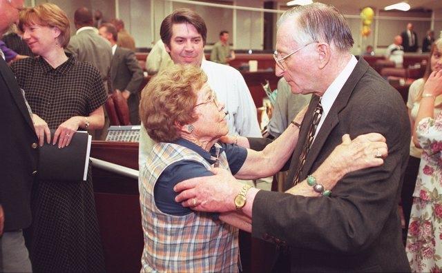 Assemblywoman Gene Segerblom, D-Boulder City, hugs Speaker Joe Dini, D-Yerington, as Scott Sherer, legal council for Gov. Kenny Guinn looks on, as the 1999 Legislative Session ends near midnight M ...