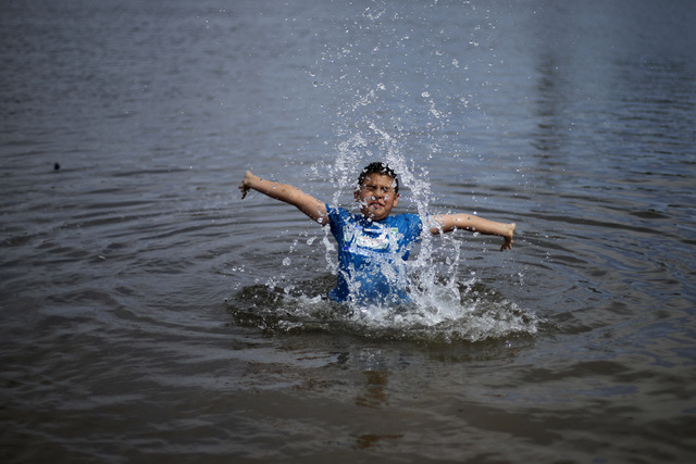 Tomas Hernandez plays in Colorado river water flowing in a normally dry riverbed Thursday, March 27, 2014, in San Luis Rio Colorado, Mexico. Colorado River water has begun pouring over a barren de ...