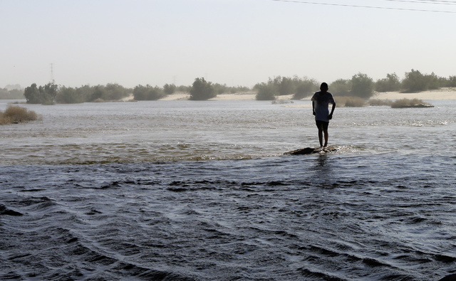 Alberto Santos crosses water in what is normal a dry riverbed Wednesday, March 26, 2014, in San Luis Rio Colorado, Mexico. Colorado River water has begun pouring over a barren delta near the U.S.- ...