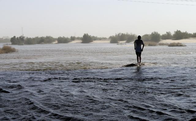 Alberto Santos crosses water in what is normal a dry riverbed Wednesday, March 26, 2014, in San Luis Rio Colorado, Mexico. Colorado River water has begun pouring over a barren delta near the U.S.- ...