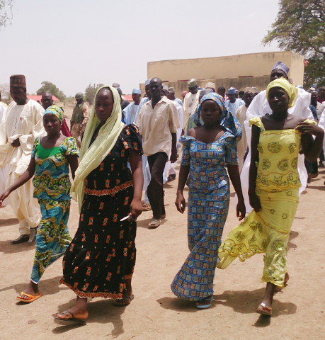 FILE - In this Monday April 21, 2014 file photo, four female students of the government secondary school Chibok, who were abducted by gunmen and reunited with their families, walk in Chibok, Niger ...
