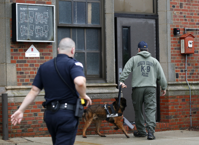 A Bergen County Police officer, right, walks with a police dog into Teaneck High School, where at least 60 students were arrested during an overnight break-in, Thursday, May 1, 2014, in Teaneck, N ...