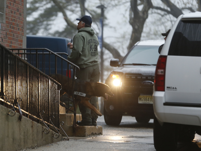 A Bergen County Police officer walks with a police dog outside of Teaneck High School, where at least 60 students were arrested during an overnight break-in, Thursday, May 1, 2014, in Teaneck, N.J ...