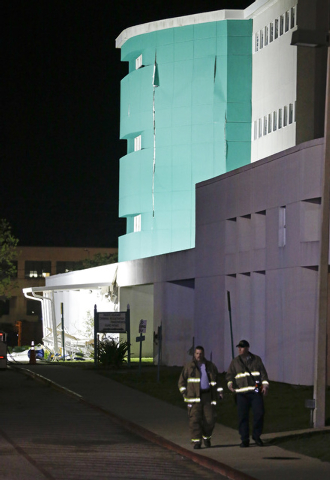 Firefighters walk the perimeter of the Escambia County Jail after an explosion caused the evacuation of the facility, Thursday, May 1, 2014, in Pensacola, Fla. Two inmates were killed in the explo ...